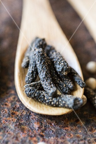 Chocolate pepper on a wooden spoon (close-up)