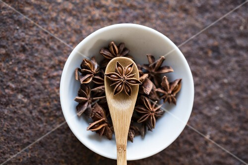 Star anise with a wooden spoon in a bowl (seen from above)