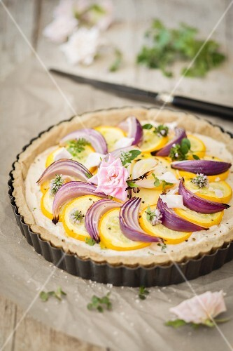 Vegan courgette tart with cashew nuts and red onions in a flan tin