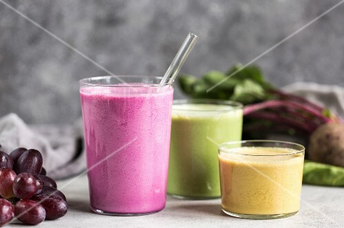 Three glasses containing colourful vegetable smoothies