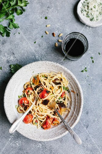 A half-eaten bowl of spaghetti with aubergine and tomatoes