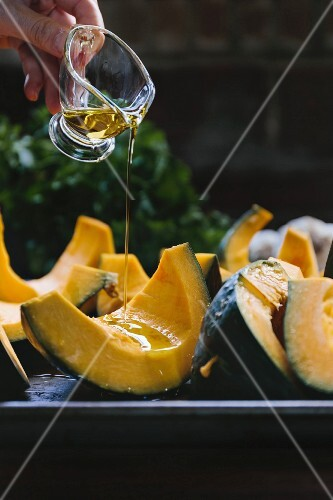 Wedges of kabocha squash being drizzled with olive oil
