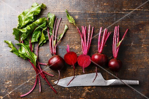 Red Beetroot with herbage green leaves and Kitchen knife on wooden background