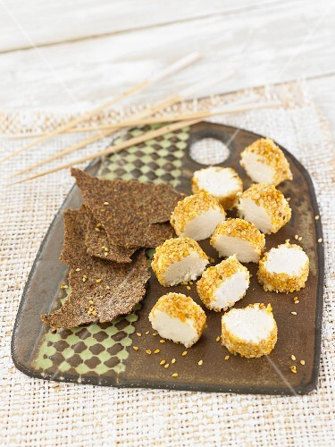 A vegan almond cheese roll cut into slices with a sesame seed crust and crackers