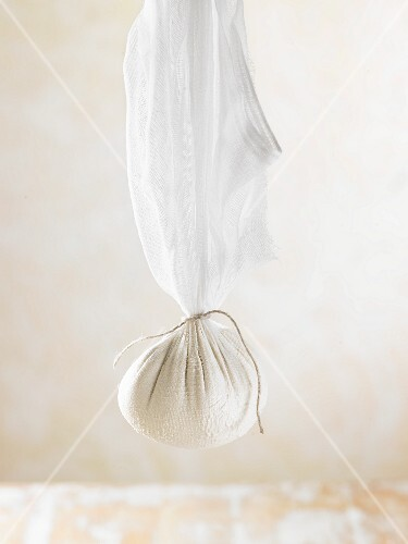 How to prepare vegan macadamia nut cheese: cheese mixture suspended in a muslin cloth to dry
