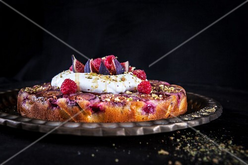 Fig upside down cake with raspberries, pistachio nuts, cream, yoghurt and honey