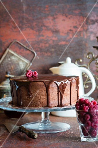 A chocolate cake with chocolate glaze and raspberries on a cake stand