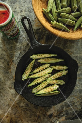 Fried okra halves in a cast iron pan