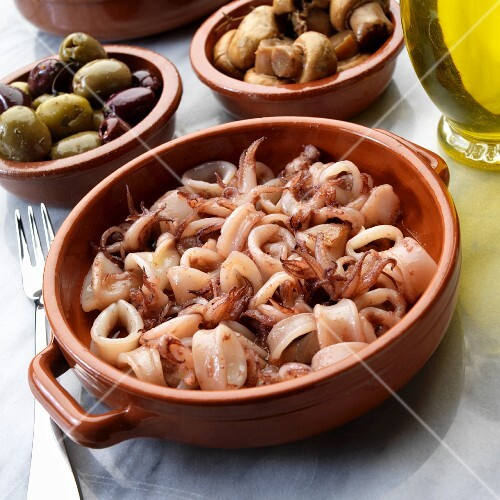 Spanish tapas: pan-fried calamari with olives and mushrooms