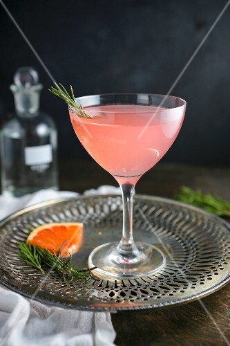 A pink grapefruit cocktail with rosemary