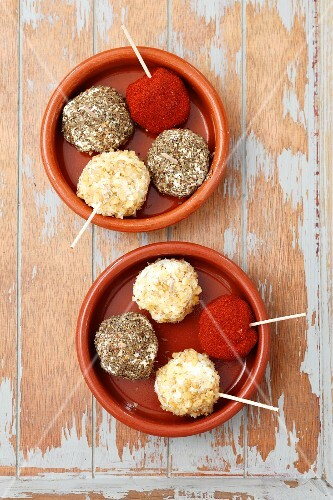 Goats' cheese balls coated in paprika powder, walnuts and dried herbs