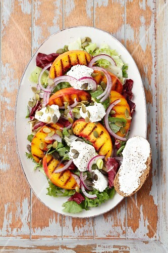 A salad with grilled peaches and goats' cheese, served with bread coated in goats' cheese