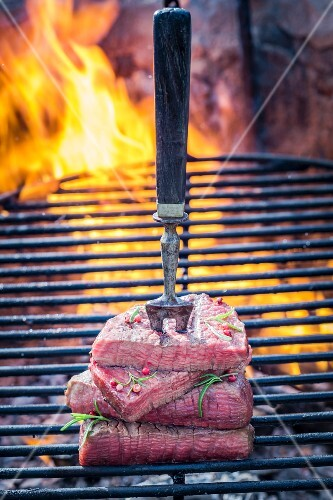 Steaks on a meat fork on a barbecue with rosemary and pepper