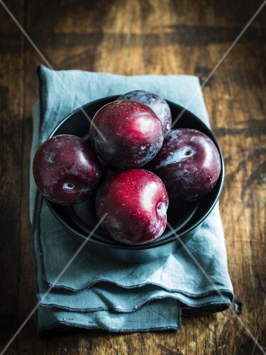 Plums in a bowl on a wooden surface
