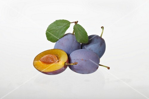 Plums, whole and halved, with leaves