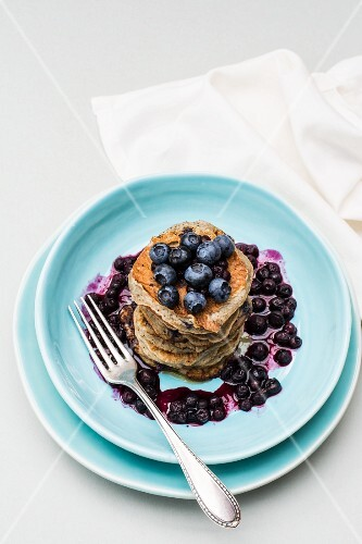 Banana pancakes with blueberries stacked on a plate