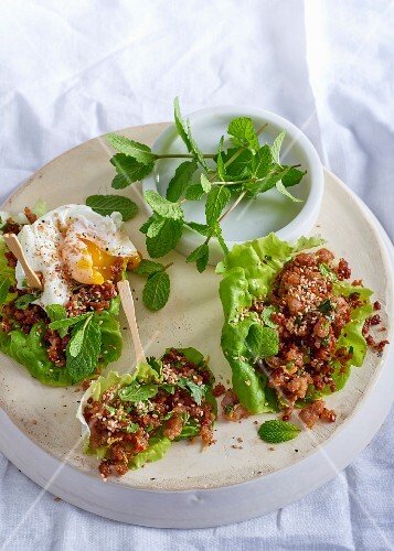 Ginger and chilli pork in lettuce cups topped with a poached egg
