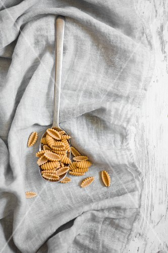 Gnocchetti pasta made of yellow peas with a spoon on a cloth