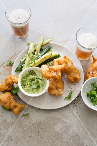 Beer-battered fish nuggets with fried baby courgettes and pesto and sour cream sauce