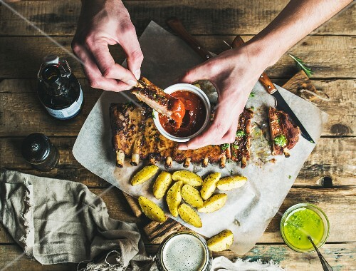 Man eating roasted pork ribs with potato pieces, garlic, rosemary and green herb sauce