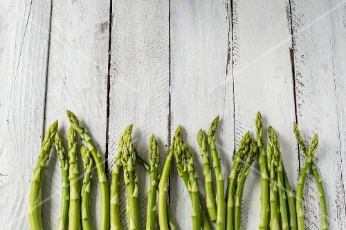 Green asparagus on white wood