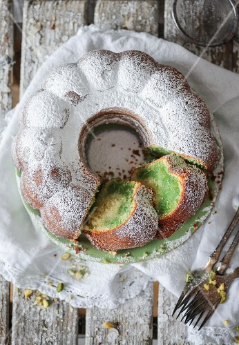 A marbled pistachio Bundt cake dusted with icing sugar, sliced