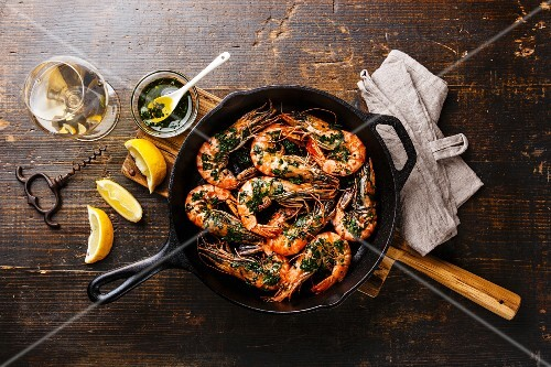 Pan-fried king prawns with herbs in a grill pan with a glass of white wine on a wooden surface