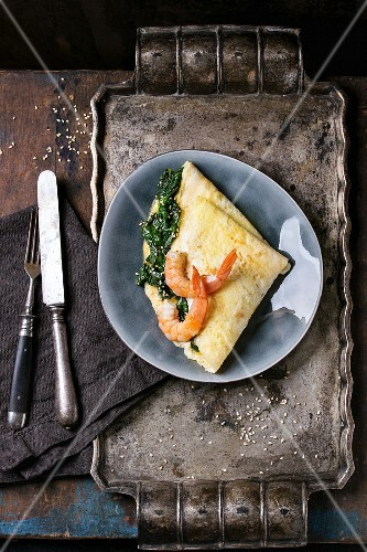 Gray oval plate with omelet staffed cooked spinach and fried shrimps prawns, served with sesame seeds