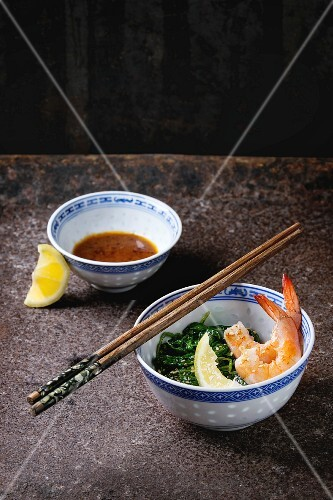 Chinese bowls with Cooked spinach and fried shrimps prawns with lemon and sesame seeds, soy sauce and chopsticks