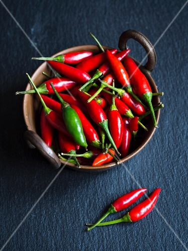 Small chilli peppers in a copper bowl on slate