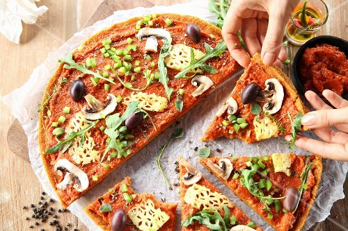 A vegan pizza with pineapple, mushrooms and olives, partly cut into slices