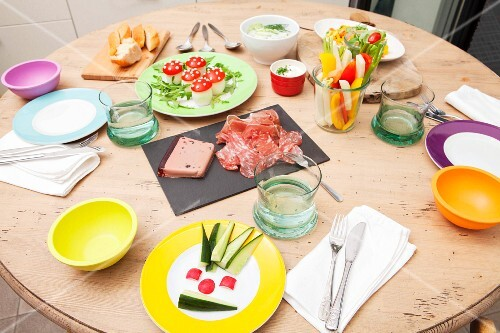 A table set for evening tea with vegetable sticks, 'toadstools' and assorted cold cuts