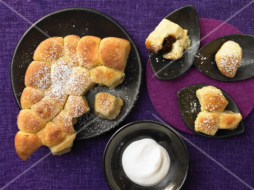 'Buchteln' (baked, sweet yeast rolls) filled with stewed damsons and served with a vanilla sauce