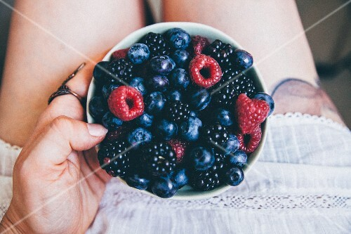 A woman holding a bowl of fresh berries