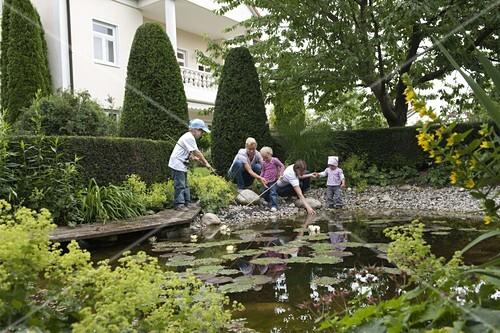Frauen und kinder beobachten wassertiere am teich for Wassertiere im teich