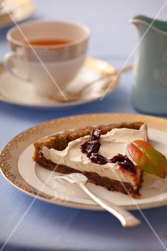 A slice of tart with dried dates, figs, walnuts, chocolate, cream and jam