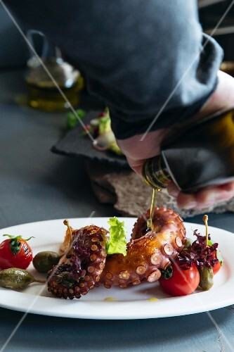 Olive oil being poured on octopus with tomatoes and giant capers