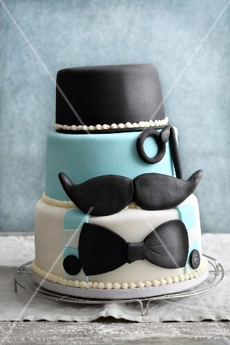 A three-tier fondant icing 'Movember' cake with moustaches