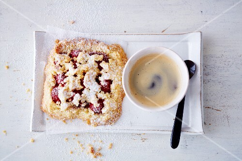 A vegan raspberry crumble slice (soya-free) served with a cup of coffee