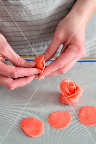 A woman's hands forming red marzipan roses