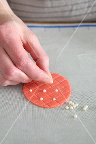 Sugar pearls being applied to a quilted pattern cake decoration