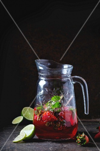 Glass jug of strawberry lemonade, served with fresh strawberries, mint and lime over dark background