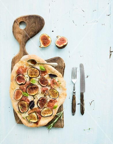 Rustic homemade pizza with figs, prosciutto and mozzarella cheese on dark wooden serving board