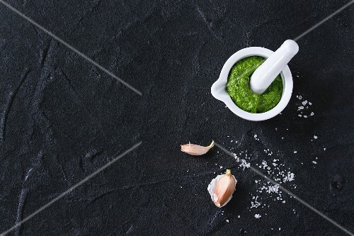 Homemade ramson green pesto sauce in white ceramic mortar with pestle over black textured background
