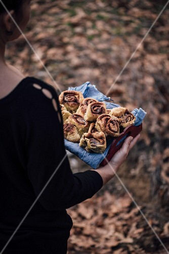 A woman holding a tray full of cinnamon rolls in the nature of dry leaves