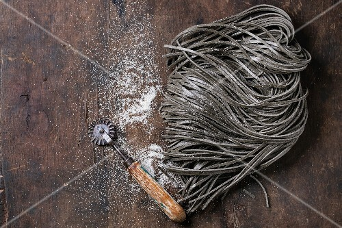 Raw uncooked black cuttlefish ink spaghetti pasta with flour and dough disk cutter over dark wooden background