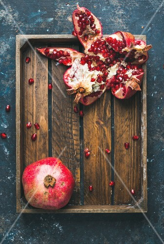 Fresh ripe pomegranates cut in pieces in rustic wooden tray