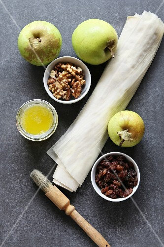 Ingredients for making apple strudel: Apple, raisins, walnuts, filo pastry and butter