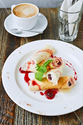 Pancakes with cottage cheese and cherry and a cup of cappuccino on wooden table