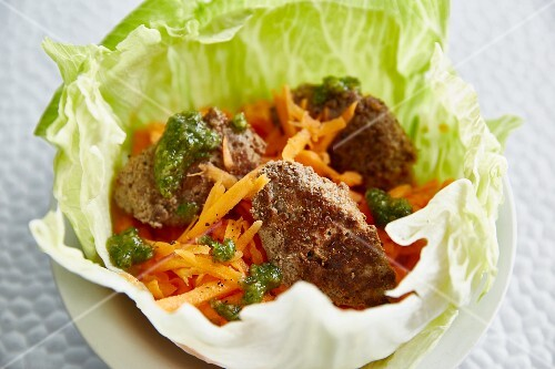 A salad bowl with meatballs and grated carrot